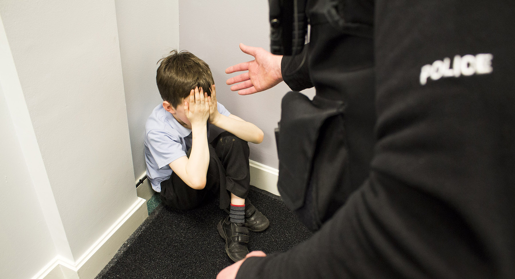 A boy sat crossed legged in the corner with a police with an outstretched arm