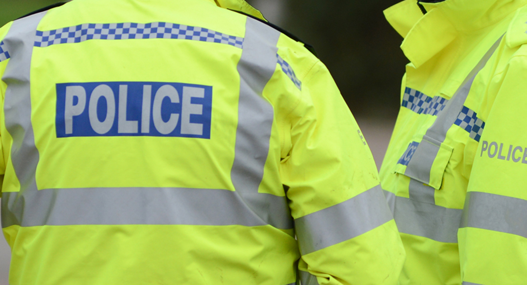 A close crop of two police officers talking in high vis police jackets